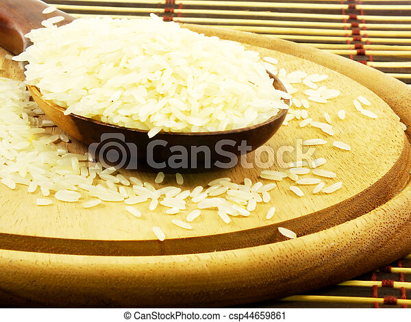 rice on wooden ladle close up - csp44659861