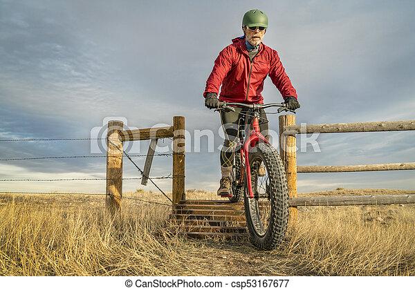 riding a mountain fat bike over cattle guard - csp53167677
