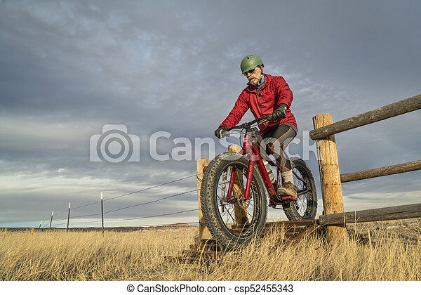 riding a mountain fat bike over cattle guard - csp52455343