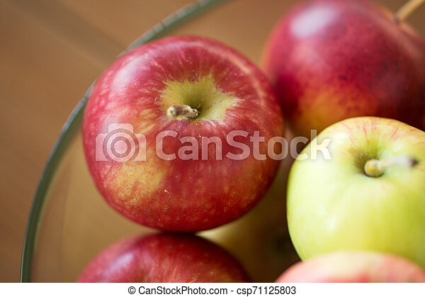 ripe apples in glass bowl on wooden table - csp71125803