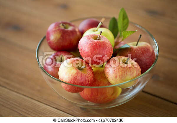 ripe apples in glass bowl on wooden table - csp70782436