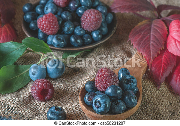 Ripe blueberries and raspberries lie in a handmade ceramic pot and a wooden spoon with a beautiful autumn leaf. - csp58231207