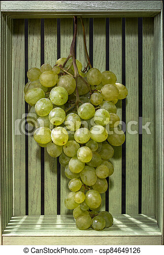 Ripe large bunch of grapes in a wooden green box - csp84649126