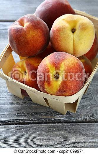 ripe peaches in a wooden crate - csp21699971