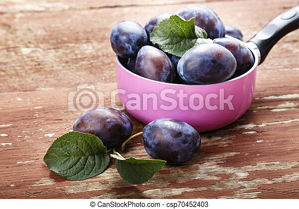 ripe plums on the table. - csp70452403