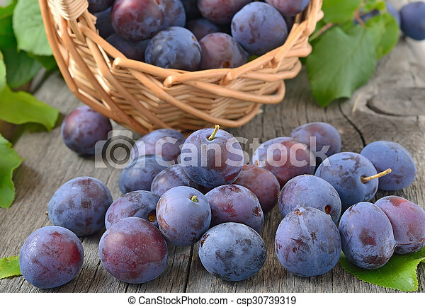 Ripe plums on the wooden table - csp30739319