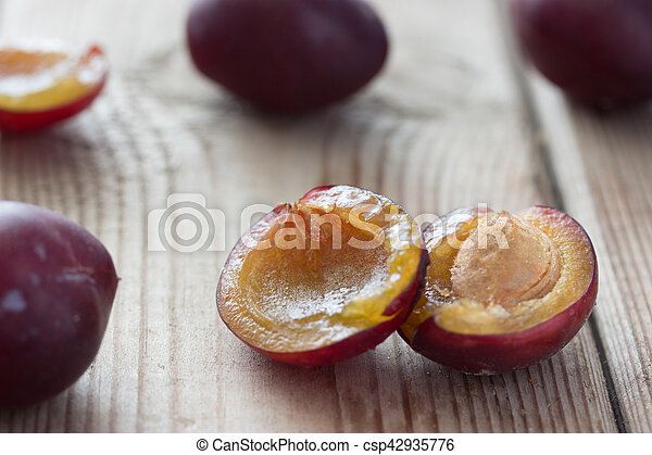 ripe plums on the wooden table - csp42935776