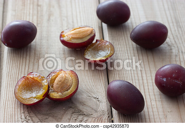 ripe plums on the wooden table - csp42935870