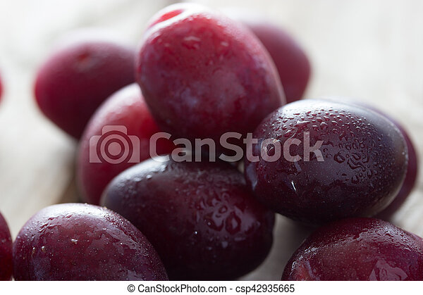 ripe plums on the wooden table - csp42935665