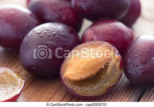 ripe plums on the wooden table - csp42935751