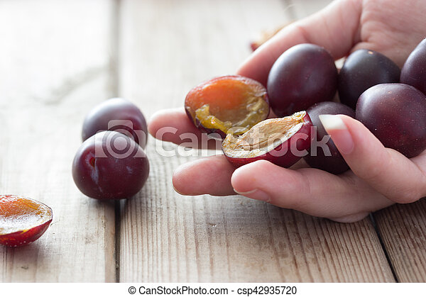 ripe plums on the wooden table - csp42935720