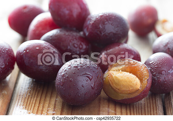 ripe plums on the wooden table - csp42935722