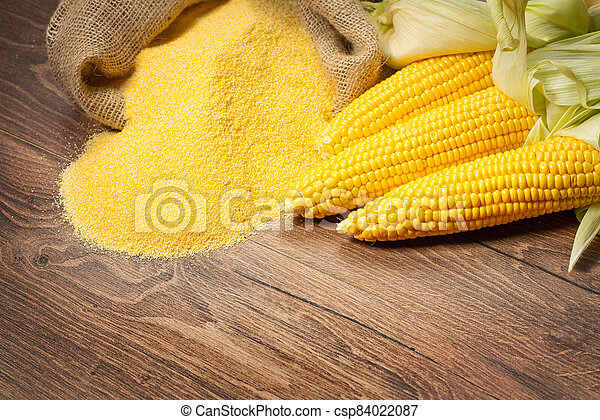 Ripe young sweet corn cob and cornmeal on wooden background - csp84022087