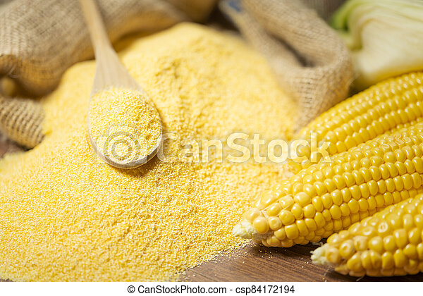 Ripe young sweet corn cob spoon and cornmeal close up - csp84172194
