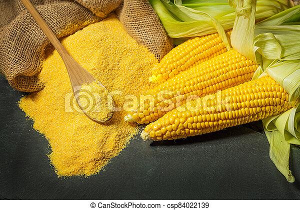 Ripe young sweet corn cob spoon and cornmeal - csp84022139