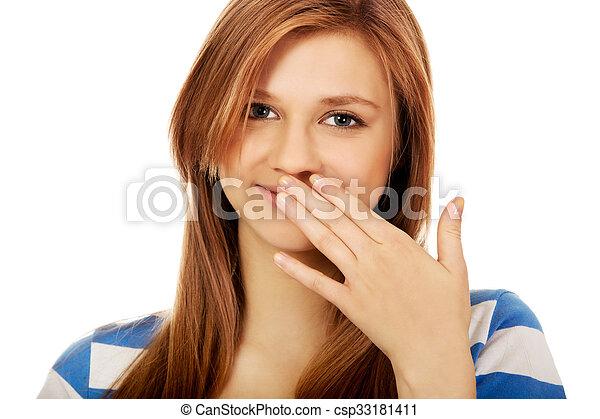 Una adolescente se ríe con la mano - csp33181411