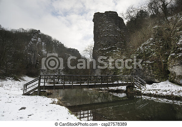 River flowing through snow covered Winter landscape in forest valley - csp27578389