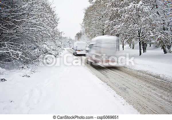 Road in deep Winter snow with blurred moving cars - csp5069651