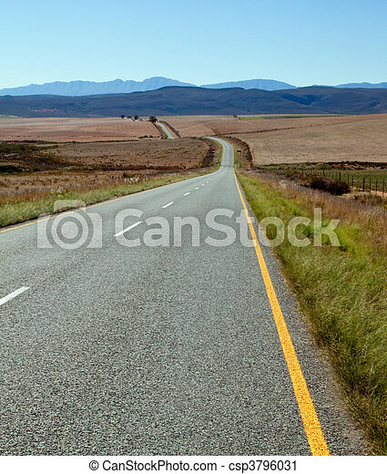 Road over farm lands in South Africa towards distant mountains - csp3796031