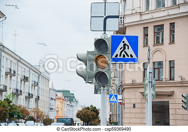 Road sign of a pedestrian crossing and traffic light with yellow light - csp59369490