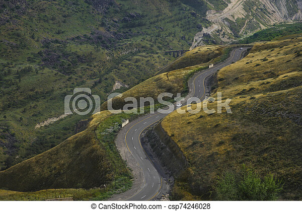 Road snaking through mountain landscape - csp74246028