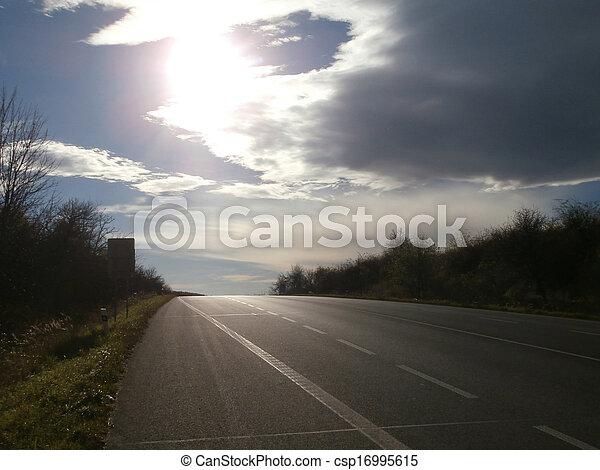Road with dark horizon in evening sun - csp16995615
