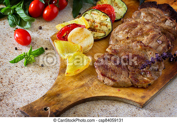 Roast beef or pork with sauce and grilled autumn vegetables: peppers, onions and eggplant on a concrete brown background. Food Concept Thanksgiving. - csp84059131