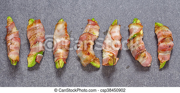 Roasted avocado pieces wrapped in bacon - csp38450902