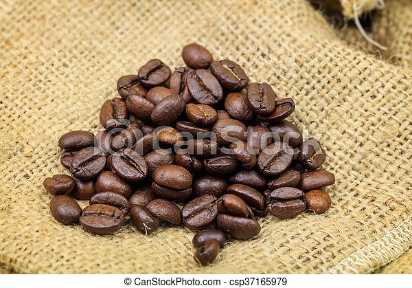 Roasted coffee beans on sackcloth background - csp37165979