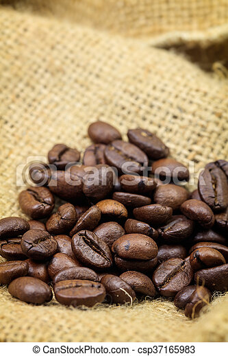 Roasted coffee beans on sackcloth background - csp37165983