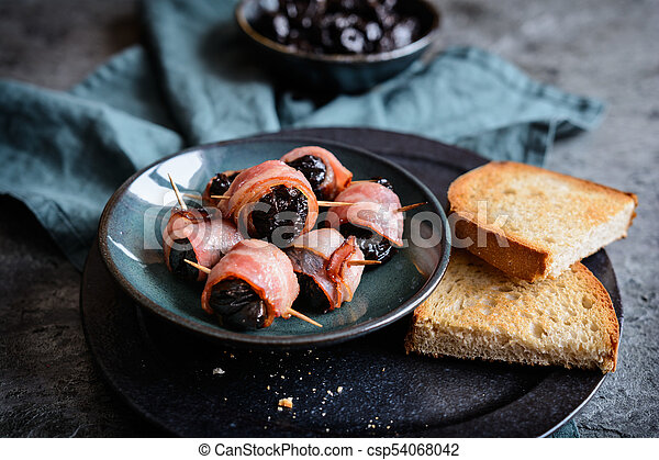 Roasted dried plums wrapped in bacon - csp54068042
