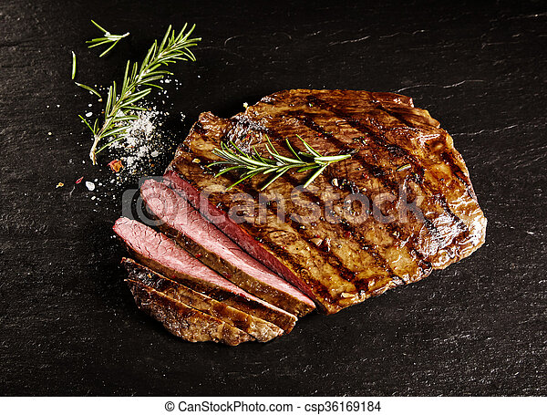 Roasted medium rare sliced flank beef with rosemary - csp36169184