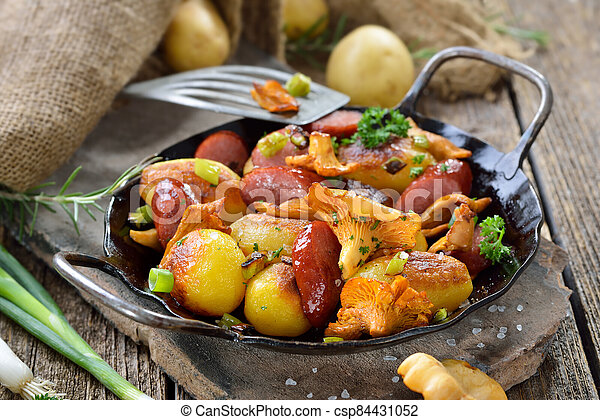 Roasted potatoes with mushrooms and sausages - csp84431052