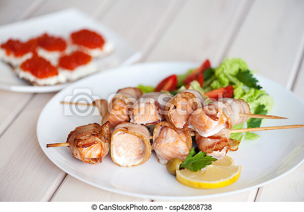 Roasted salmon meat pieces wrapped in bacon slices - csp42808738