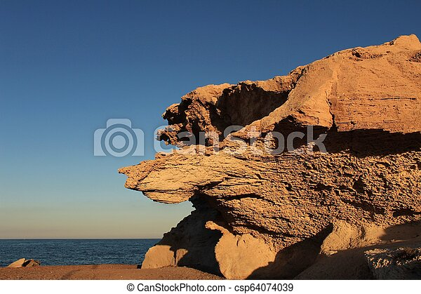 Rock formations on the beach at sunset - csp64074039