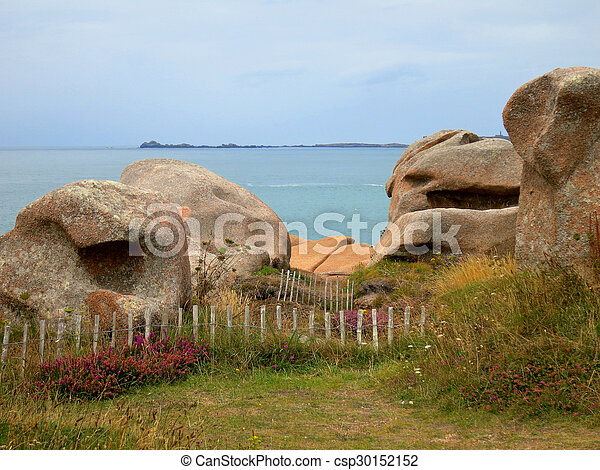 Rocks behind a fence at cote de granite rose, brittany... stock ...