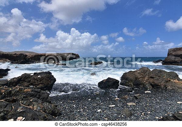Rocks Scattered Across Aruba's Black Sand Stone Beach - csp46438256