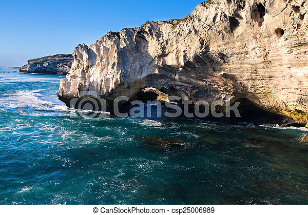 Rocky cove and ocean wave crashing into an eroded arch - csp25006989