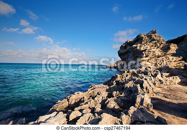Rocky cove and ocean wave crashing into an eroded arch - csp27467194
