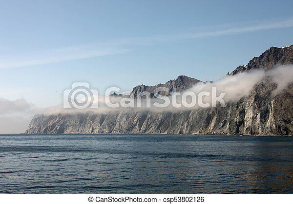Rocky shore of the Okhotsk sea in the morning mist. - csp53802126