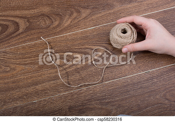 Roll of brown linen string on brown background - csp58230316