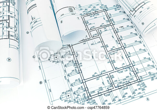 Rolled Building Plans On Architectural Blueprint Background Stock Photo
