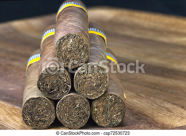 rolled cigars from a tobacco leaf on a wooden background - csp72530723