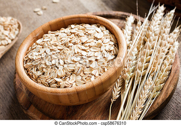 Rolled oats or oat flakes and golden wheat ears on wooden background. - csp58676310