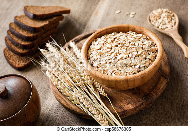 Rolled oats or oat flakes and golden wheat ears on wooden background. - csp58676305
