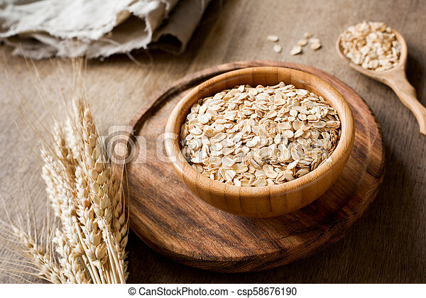 Rolled oats, organic oat flakes in wooden bowl and golden wheat ears on wooden background - csp58676190
