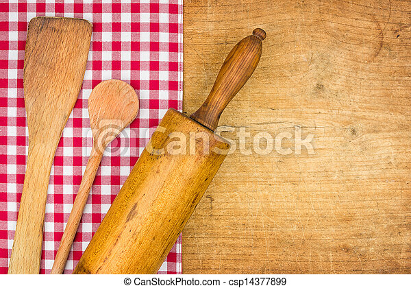 Rolling pin with wooden spoon on a wooden board with a checkered tablecloth - csp14377899