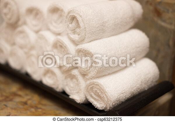 Rolls of white cotton towel in bedroom. - csp63212375