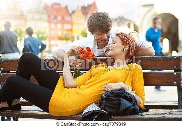 Una pareja joven y romántica relajándose al aire libre sonriendo - csp7079319