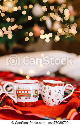 Romantic atmosphere and hot cocoa cups. Holiday lights and red plaid - csp77089720